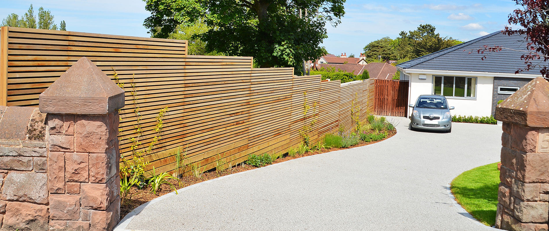 Contemporary Driveway on a Slope Fenced in Using Western Red Cedar Slatted Screens